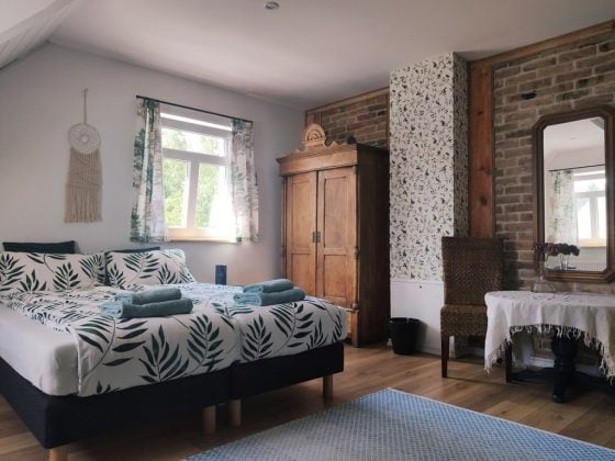drewniana szaga, ściany z cegły i tapeta w liście na drugiej ściane,
