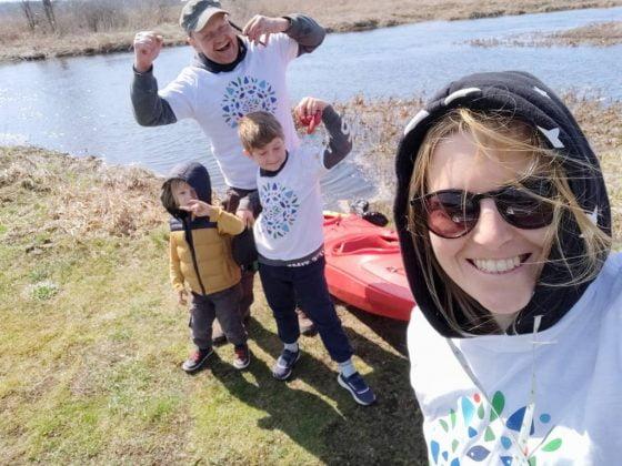 kobieta, mężczyzna i dwójka dzieci stoją na brzegu jeziora i uśmiechają się