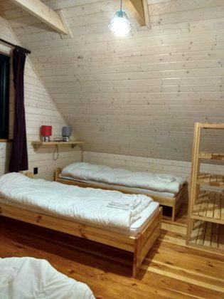 pokój z dwoma drewnanianymi łóżkami i szfką