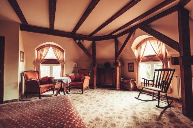 pokój sypialnia, łóżko, fotele i stolik, fotel bujany, drewno na suficie