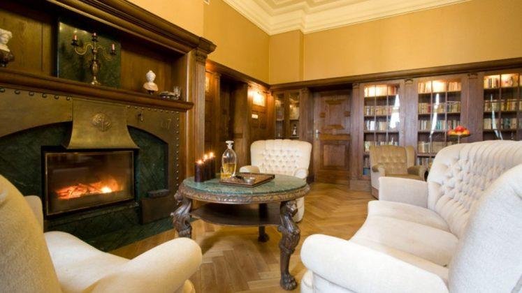 kominek, stolik i piękne, stare fotele , przy ścianach książki na regałach