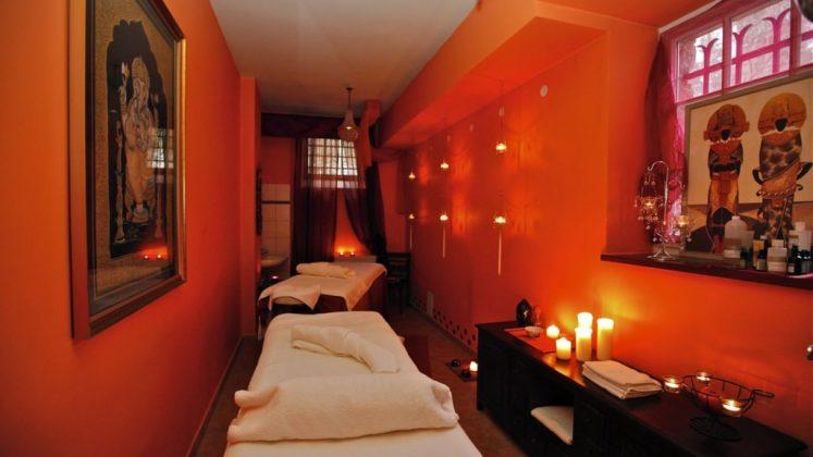 pokój do masażu, łóżko do masażu, zapalone świece