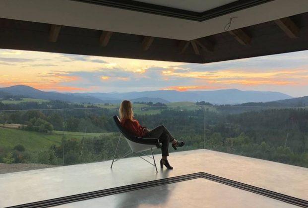 kobieta siedzi na tarasie przed nią widok na góry