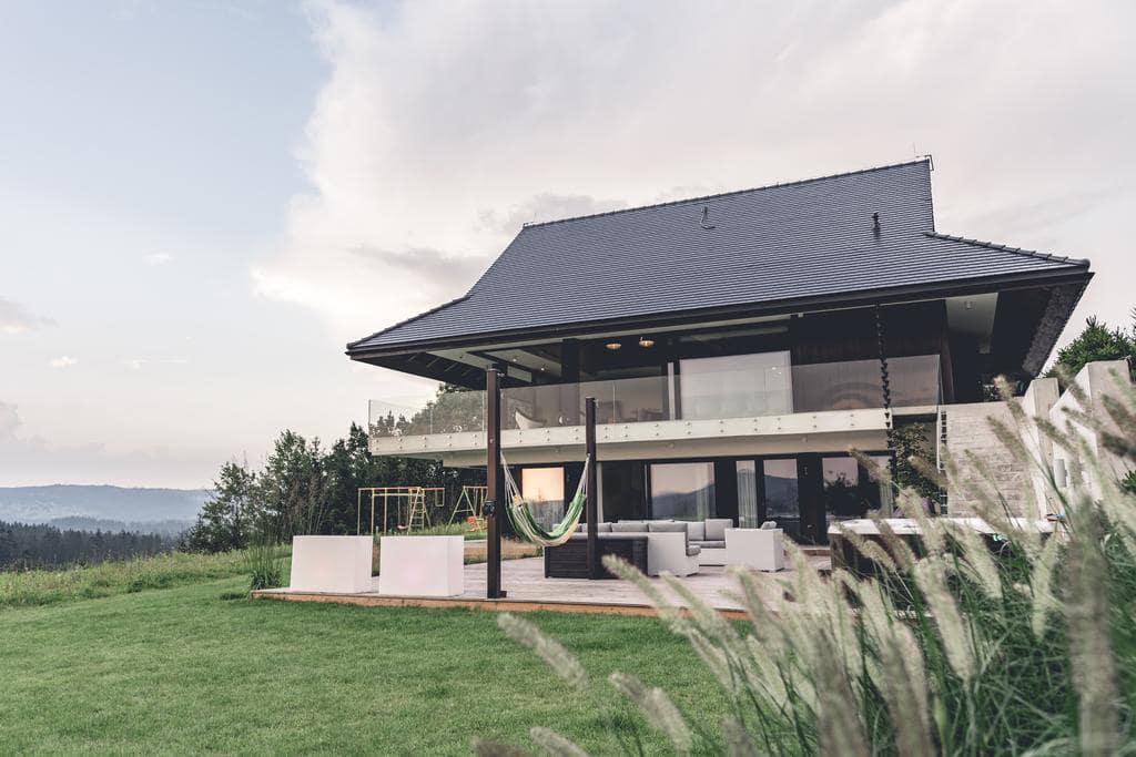 dom z dużymi przeszklonymi ścianami z widokiem na góry