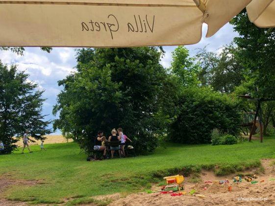 piaskownica, łąka, parasol ogrodowy z napisem Villa Greta