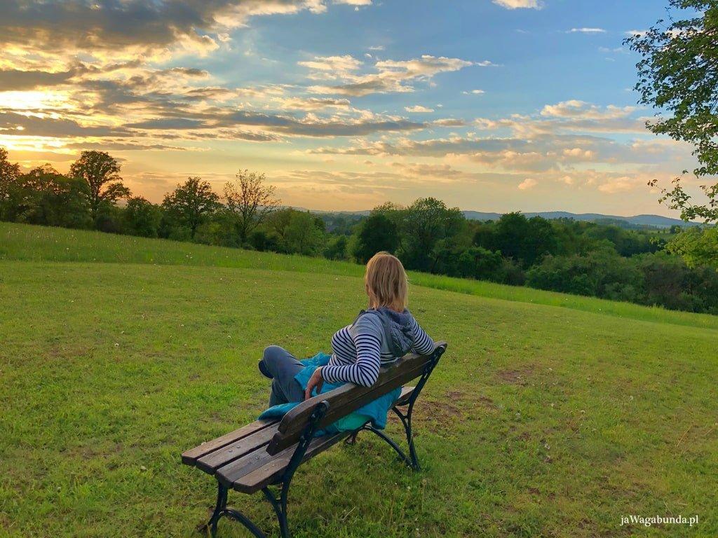 kobieta siedzi na ławce na wzgórzu z widokiem na góry