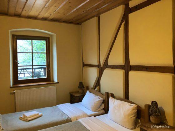 pokój z drewnianymi listwami na ścianach, dwa łóżka z białą pościelą
