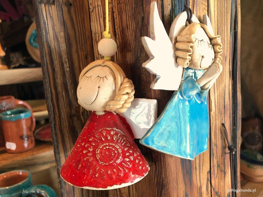 dwa kolorowe ceramiczne anioły zawieszone na sznurkach na drewnianym słupie
