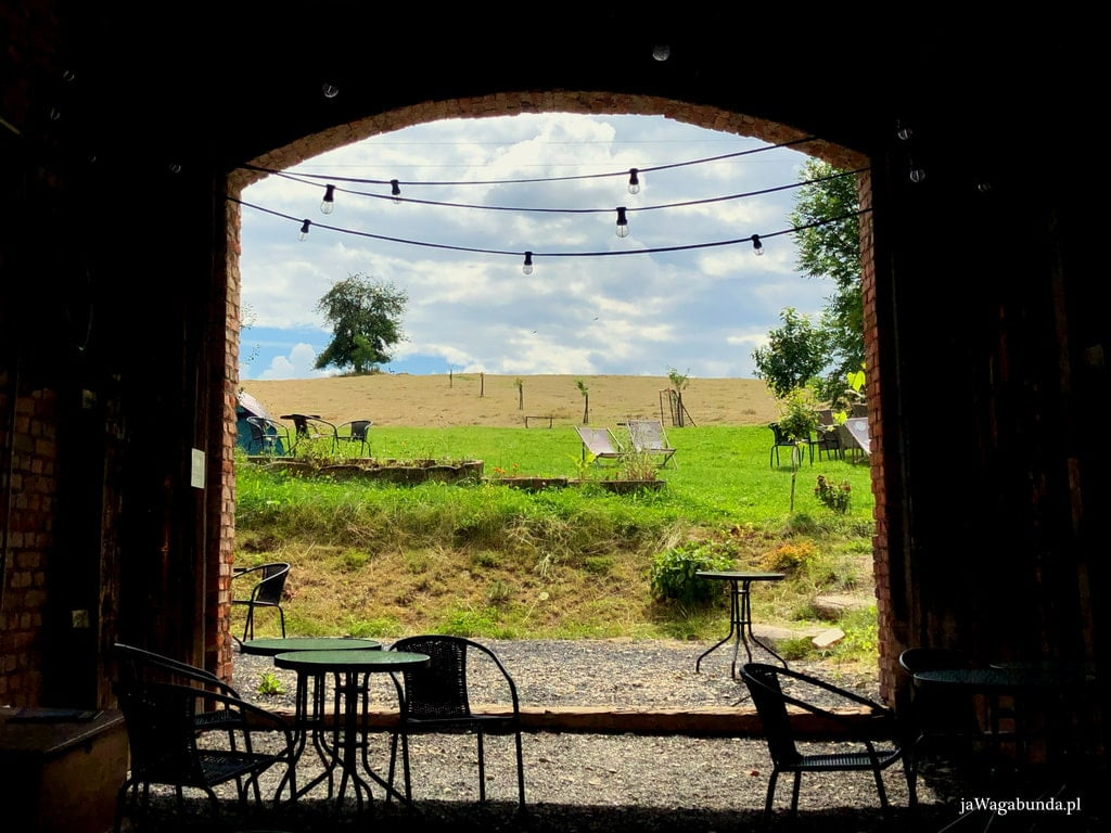 widok na łąkę przez otwarte drzwi stodoły