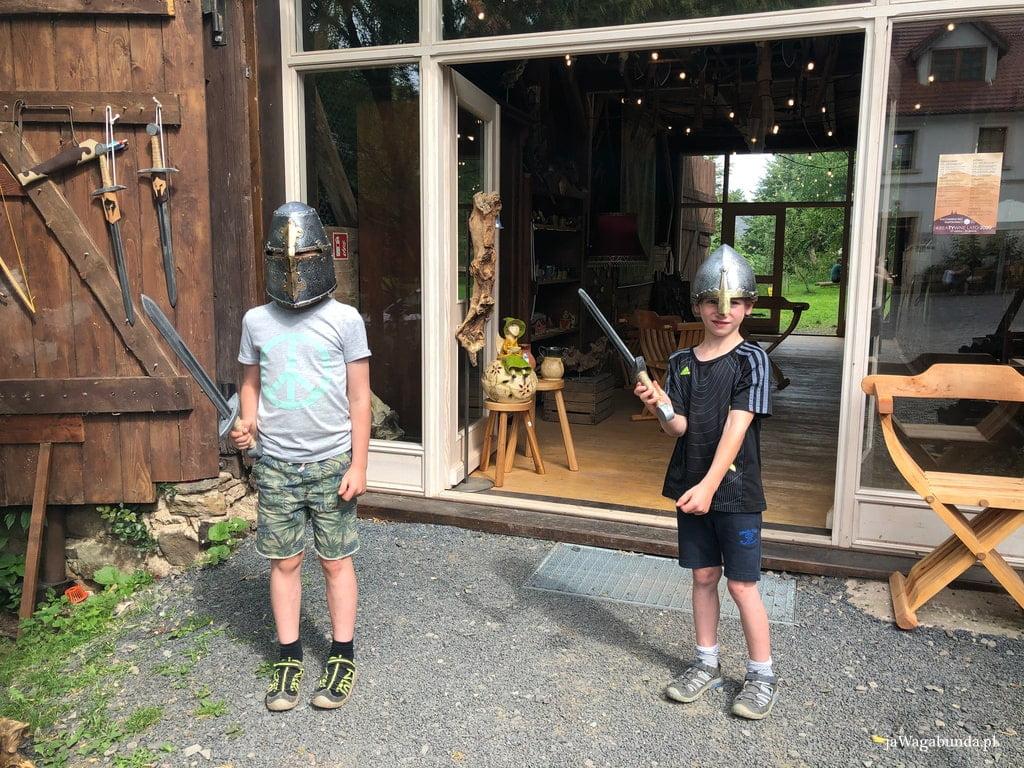 dwaj chłopcy w hełmach i z szablami plastikowymi w dłoniach