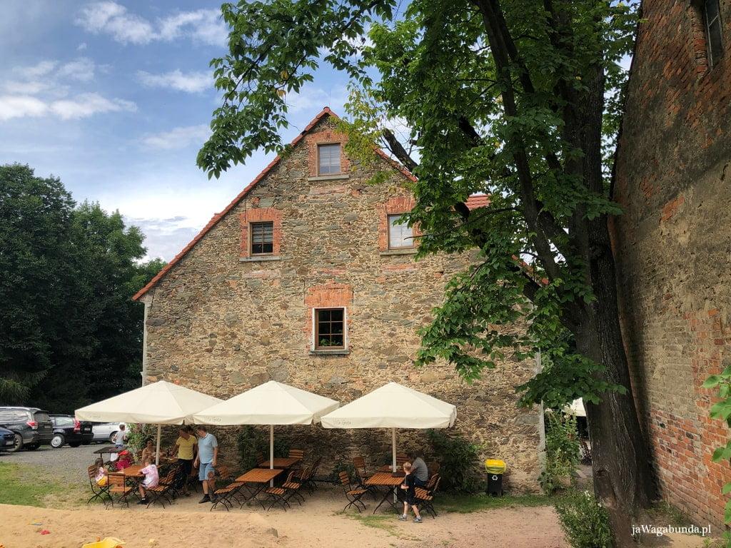 kamienny dom a przed nim stoły i parasole, przy których można jeść posiłki
