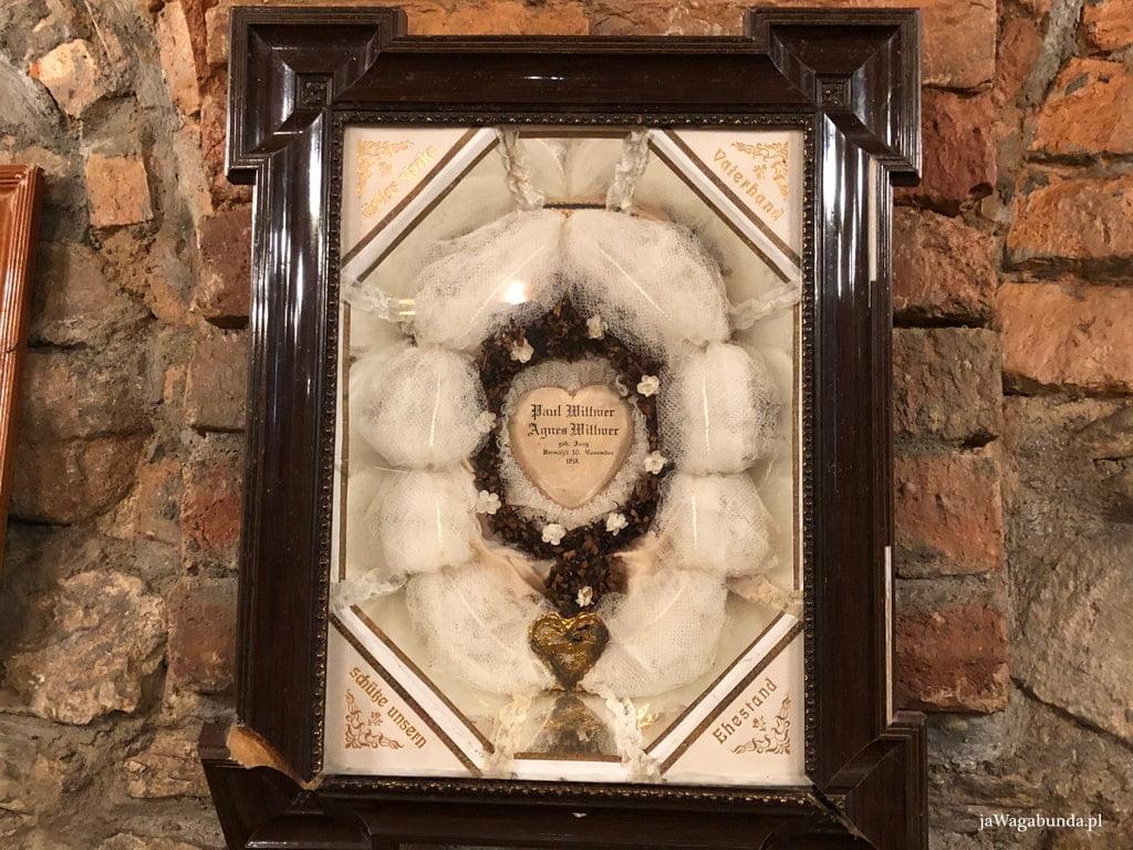 wianek ślubny oprawiony w drewnianą ramkę i powieszony na ścianie jako pamiatka slubu
