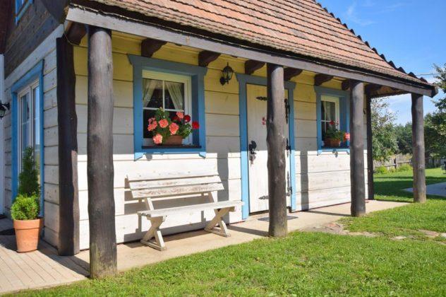 biały domek drewniany przed domem ławeczka