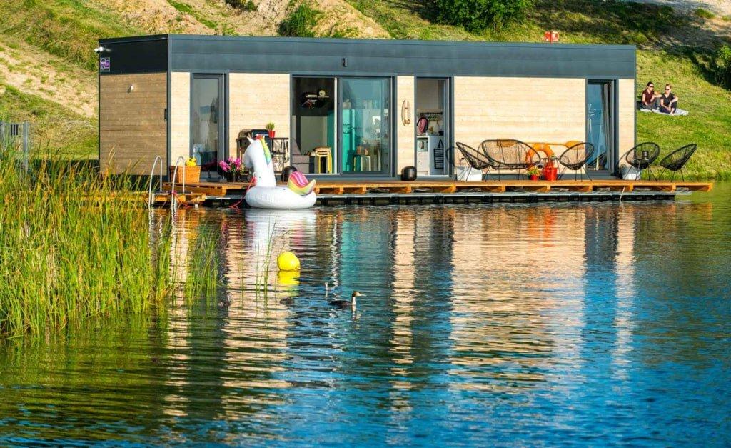 Dom na wodzie położony w pobliżu brzegu jeziora, przed nim dmuchany łabędź dla dzieci