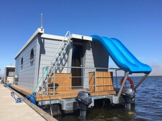 Dom na wodzie zacumowany przy nabrzeżu ze zjeżdżalnią do wody