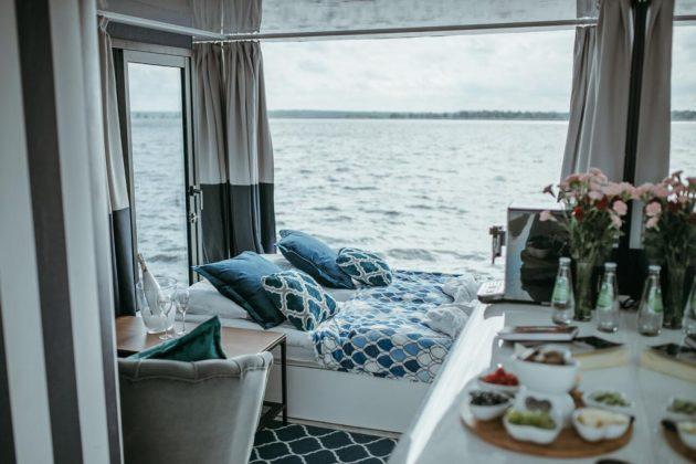 łóżko do spania, a za szybą widoczne jezioro
