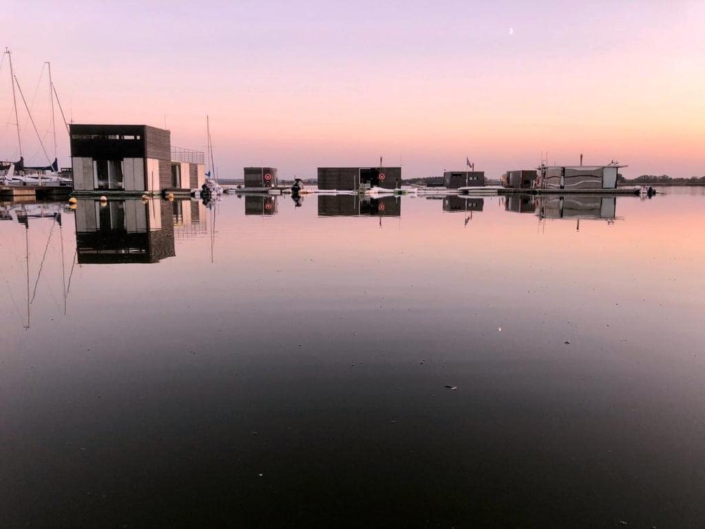 Pływające domki na wodzie oświetlone zachodzącym słońcem