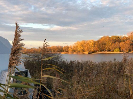 kopuła namiotu glampingu w szuwarach i widok na jezioro