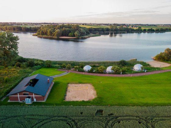 dom i kilka namiotów glamping położone nad jeziorem a widziane z lotu ptaka