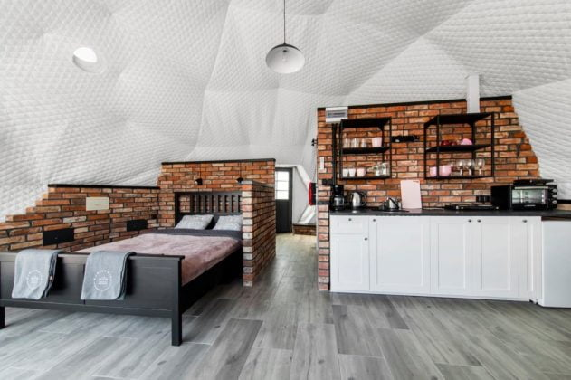 podwójne łóżko i kuchnia z wyposażeniem w glampingu