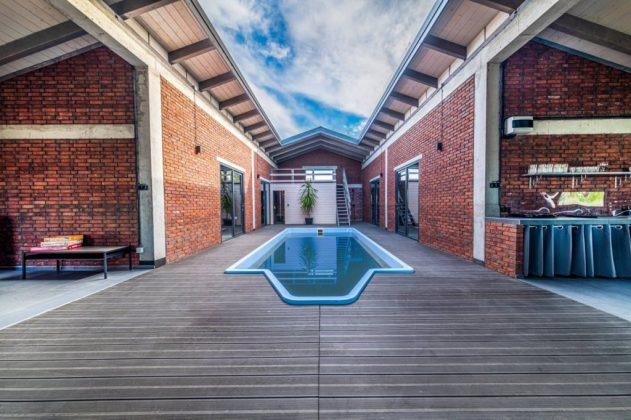 basen w domu do wynajęcia, wokół taras i przestrzeń kuchenna i wypoczynkowa