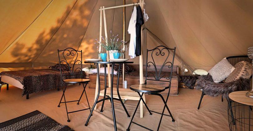 krzesła, stół i wieszak na ubrania w ładnym wnętrzu glamping