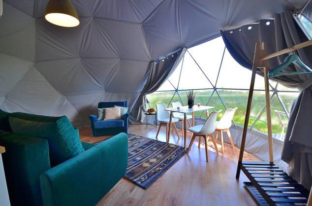 kanapa i stół z krzesłami w namiocie - glampingu z widokiem na zieleń