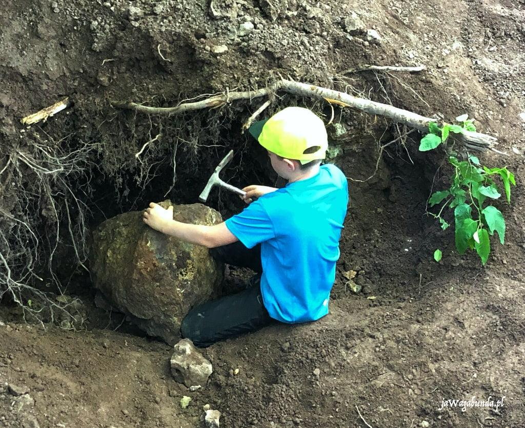 chłopiec rozbija duży kamień szuka agatów