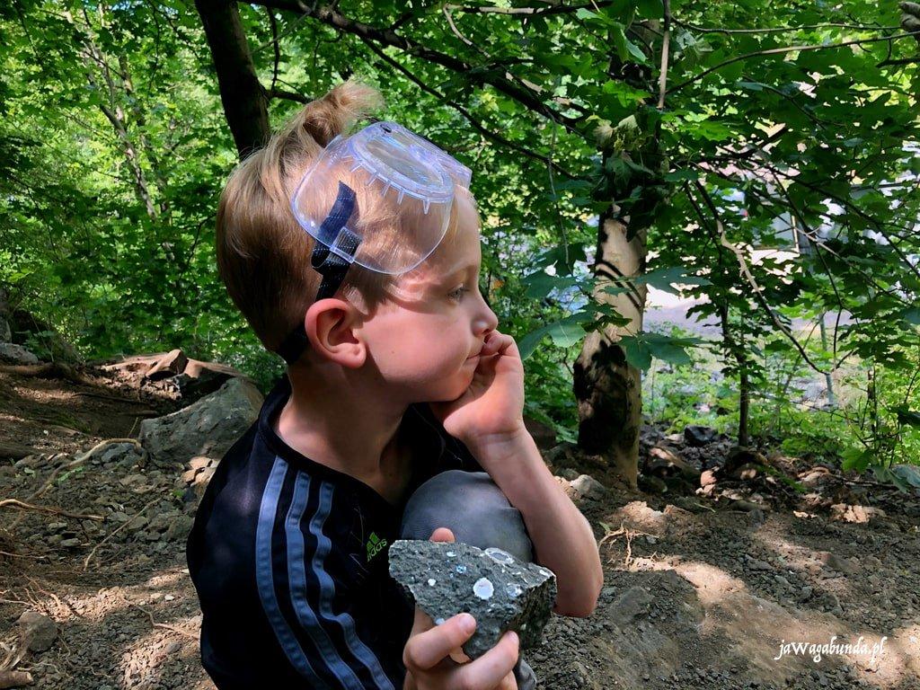 zadumany chłopiec w okularach ochronnych w ręce trzyma kamień z agatami