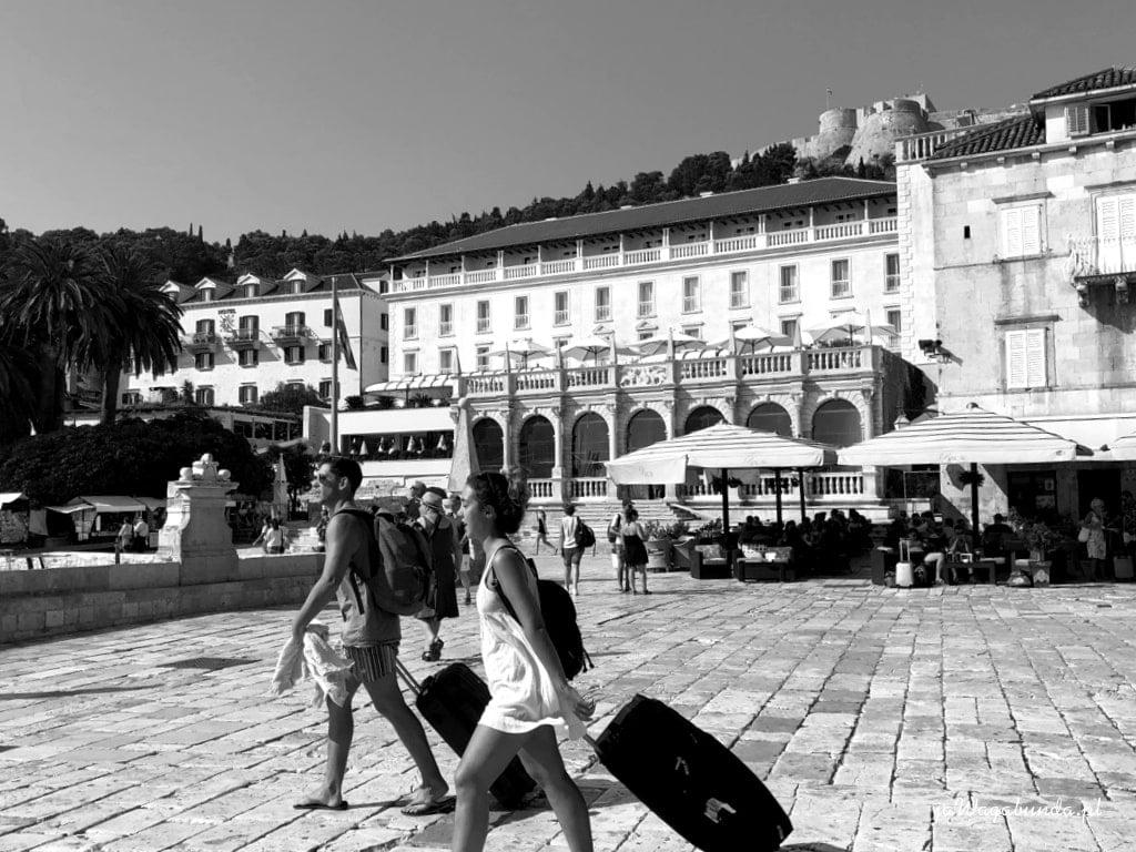 Dwie osoby ciągną walizki przez brukowany plac