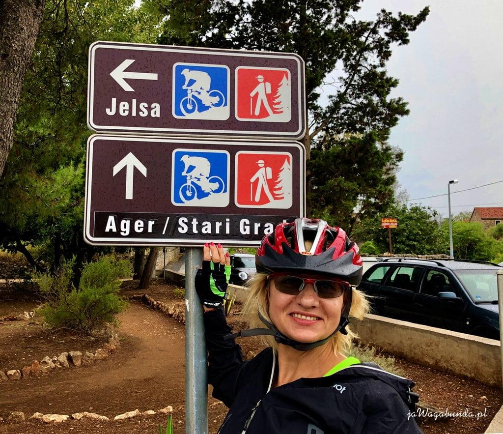 kobieta w kasku rowerowym przy tablicy ze ścieżkami rowerowymi