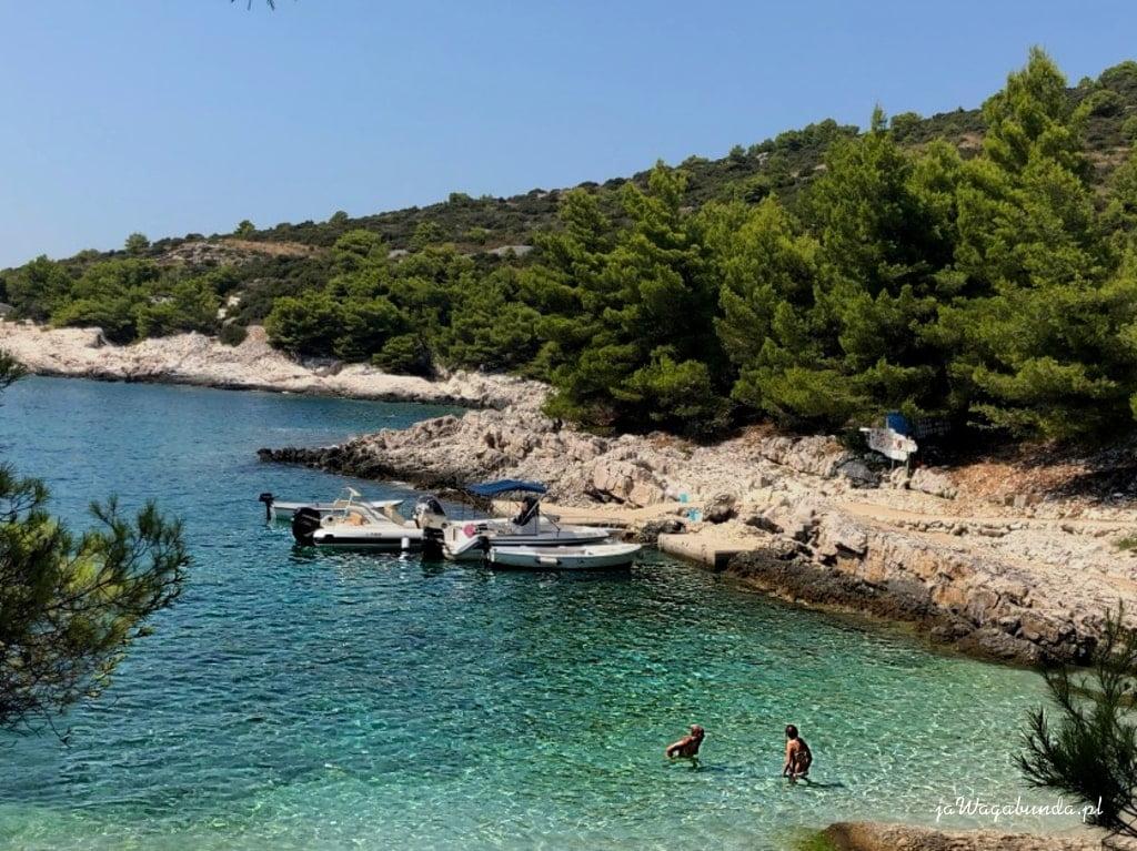 turkusowe morze, łódki i skalisty brzeg porośniety lasem