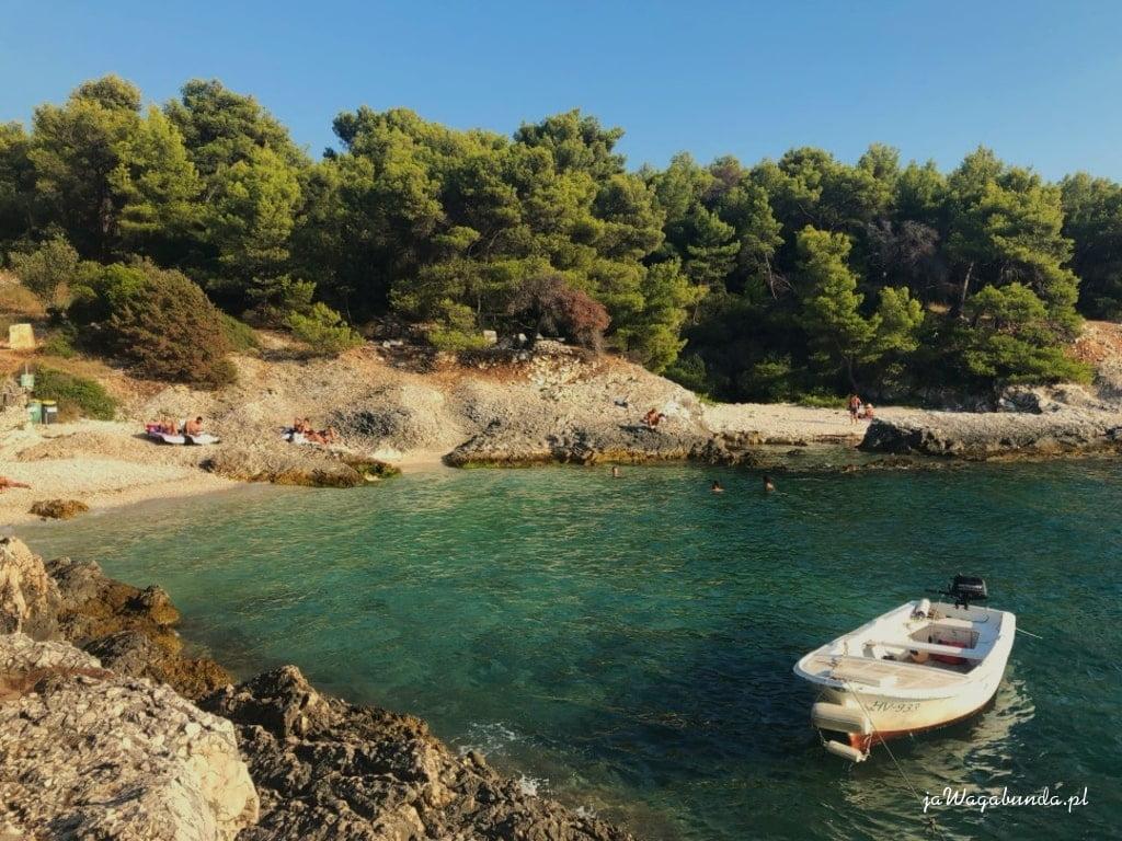 łódka, turkusowe morze i skalisty brzeg