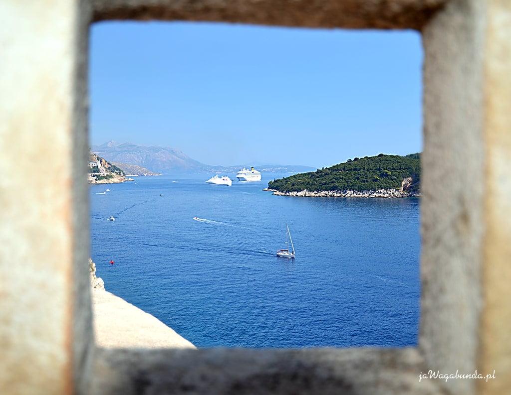 widok przez okno w murach na niebieski Adriatyk
